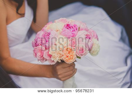 Bride holding bright wedding peony bouquet
