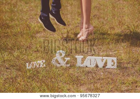Feet of groom and bride and white love letters