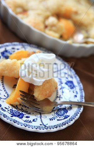 Fresh peach cobbler with whipped cream