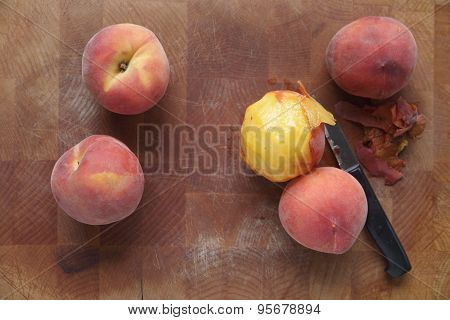 Ripe summer peaches, one peeled