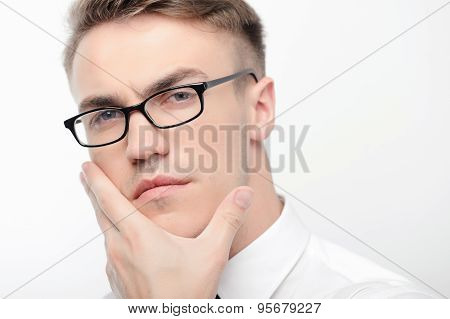 Close-up of man in glasses touching his face