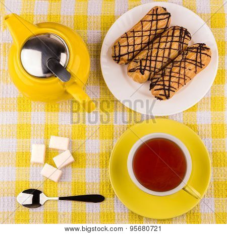 Hot Tea In Cup, Sugar Cubes And Eclairs On Table