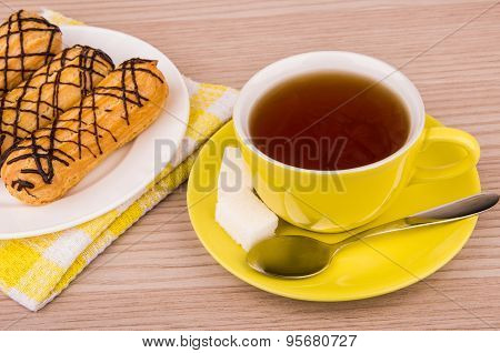 Tea In Cup, Sugar And Eclairs On Wooden Table