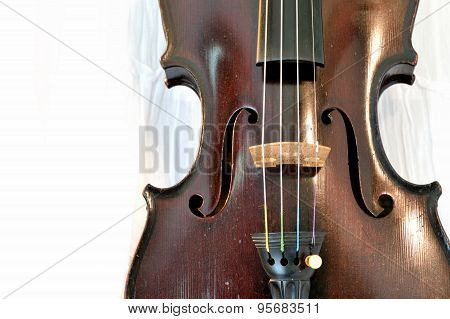 Antique Violin Closeup Against White Fabric
