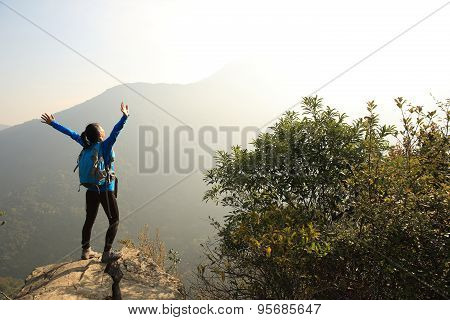 cheering woman hiker open arms at mountain peak