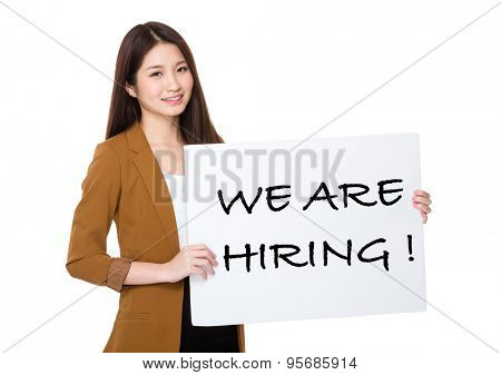 Businesswoman hold with palcard and presenting phrase of we are hiring