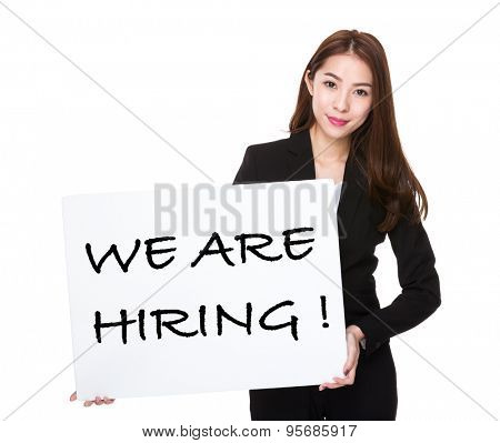 Business woman with a board for phrase of we are hiring