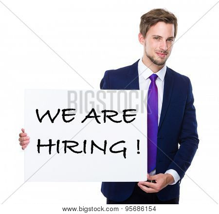 Man with white banner presenting phrase of we are hiring