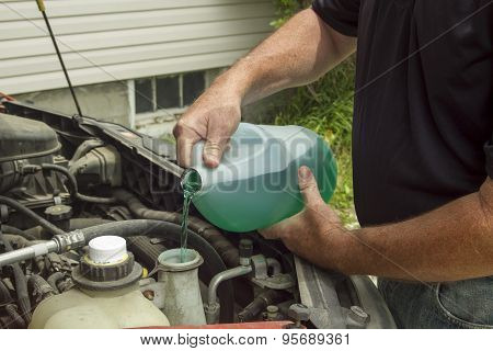 Mechanic Refilling Windershield Wiper Fluid In A Car