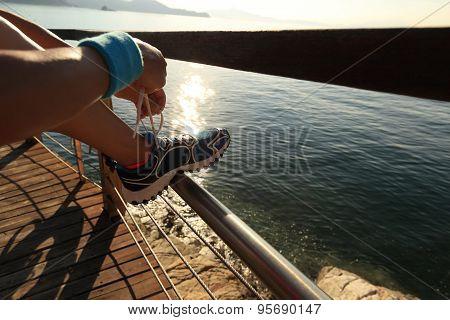 young fitness woman tying shoelace on seaside wooden boardwalk