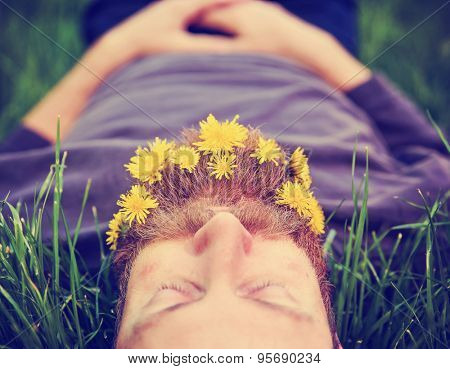 a sleeping hipster lying in tall grass with dandelions in his epic beard taking a nap toned with a retro vintage instagram filter and light leaks