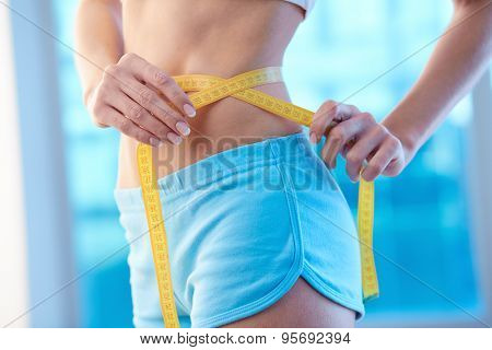 Waist of slim female with measuring tape around