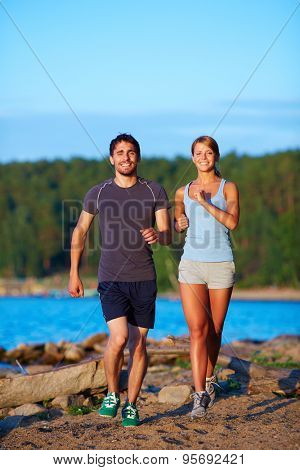 Young couple running down sandy beach