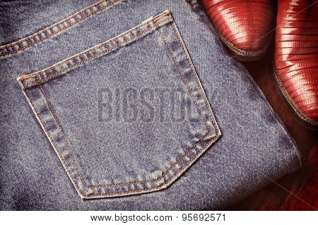 Closeup of a pair of blue jeans and cowboy boots with a faded retro look.