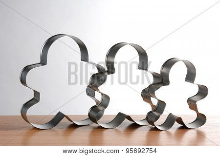 Three gingerbread man cookie cutters all different sizes against a light to dark gray background. Horizontal format.