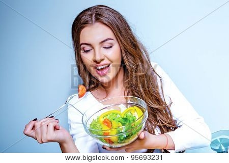 pretty young woman eating salad of vegetables, against blue background