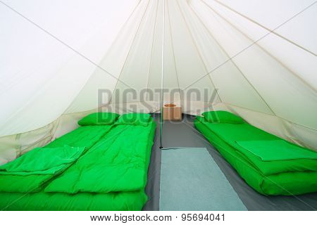 Interior white tent for guests with green sleeping bags and inflatable mattresses