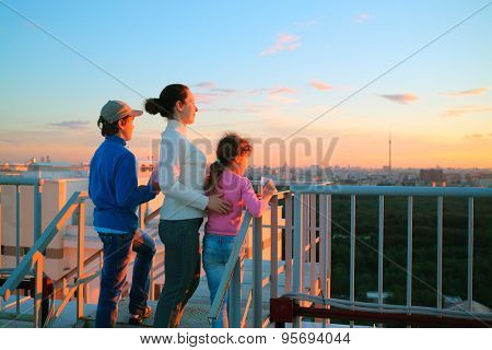 Mother with son and daughter standing on roof of multistory house and looking into distance