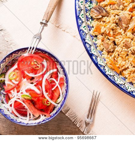 Pilaf And Achichuk Salad In Handmade Plate On Wooden Background