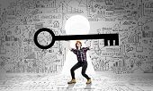 picture of keyhole  - Young woman builder and keyhole at background lifting big key above head - JPG