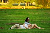 Couple Laying On Park Lawn