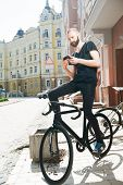 stock photo of cartographer  - Attractive man with beard is sitting on the bicycle - JPG
