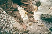 foto of survival  - Feet Man trekking boots hiking outdoor Lifestyle Travel survival concept with river and stones on background top view - JPG