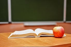 picture of classroom  - Open book and red apple lying on the desk in the classroom - JPG
