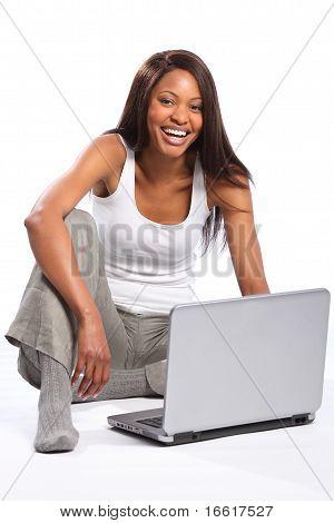 Happy black woman using laptop