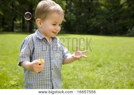 Laughing Kid Catches Soap Bubbles