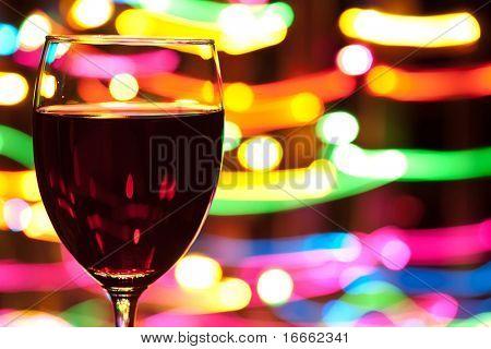 Glas Wein mit verwaschenes Bewegung Lichter im Hintergrund