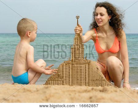 madre con hijo construir arena partiendo con aguja de collage de playa