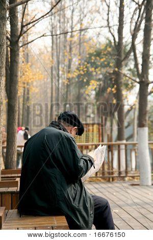 elderly man reading his newspapers