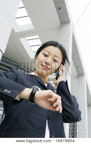 business women holding a mobile and look at her watch