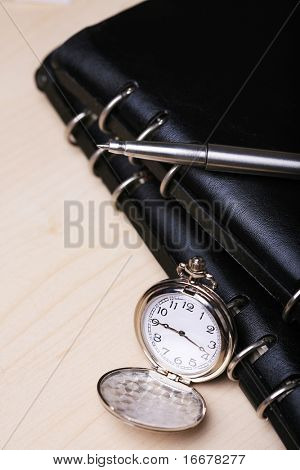 pocket watch,pen with black notebook