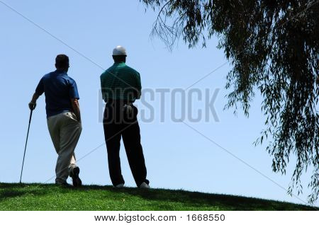 Golfers Stand At Top Of Elevated Green