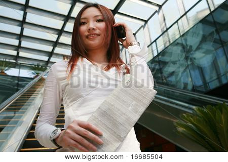 young asian business women holding mobile phone and newspaper