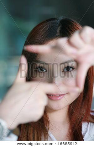 Pretty young asian woman showing thinking outside the square