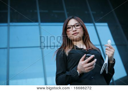 young businesswoman holding newspaper and mobile phone standing before office building