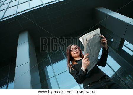 young asian business woman reading newspaper