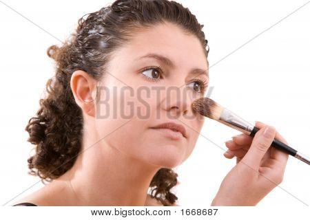 Beautiful Brunette Applying Foundation