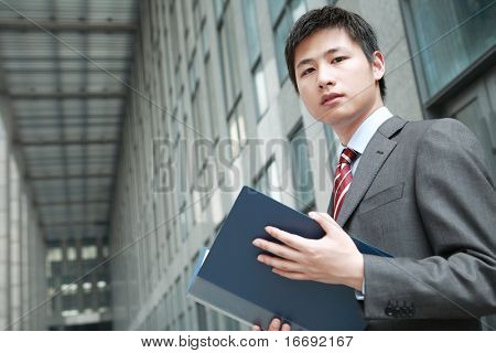 a yong Asiatic businessman  is reading document outdoor