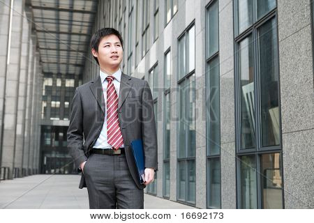 a yong Asiatic businessman  is walking outdoor