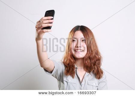Beautiful woman taking a photograph by the phone