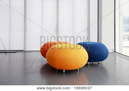 three different color rounded sofas isolated in morden house