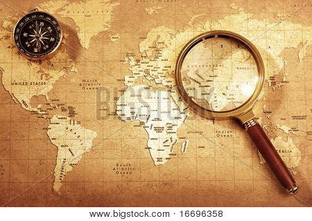 An old brass compass on a Treasure map background ,with Magnifier