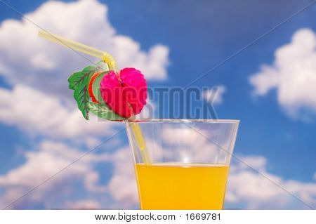 Orange Juice With Straw Against Cloudy Sky