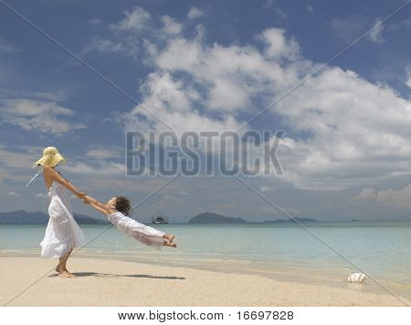 woman and girl on the beach near the water playing