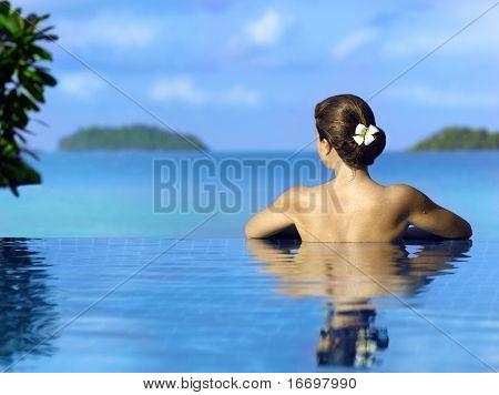 Frau im Schwimmbad in der Nähe des Ozeans