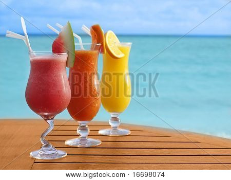 three fresh juiceson the beach on the table